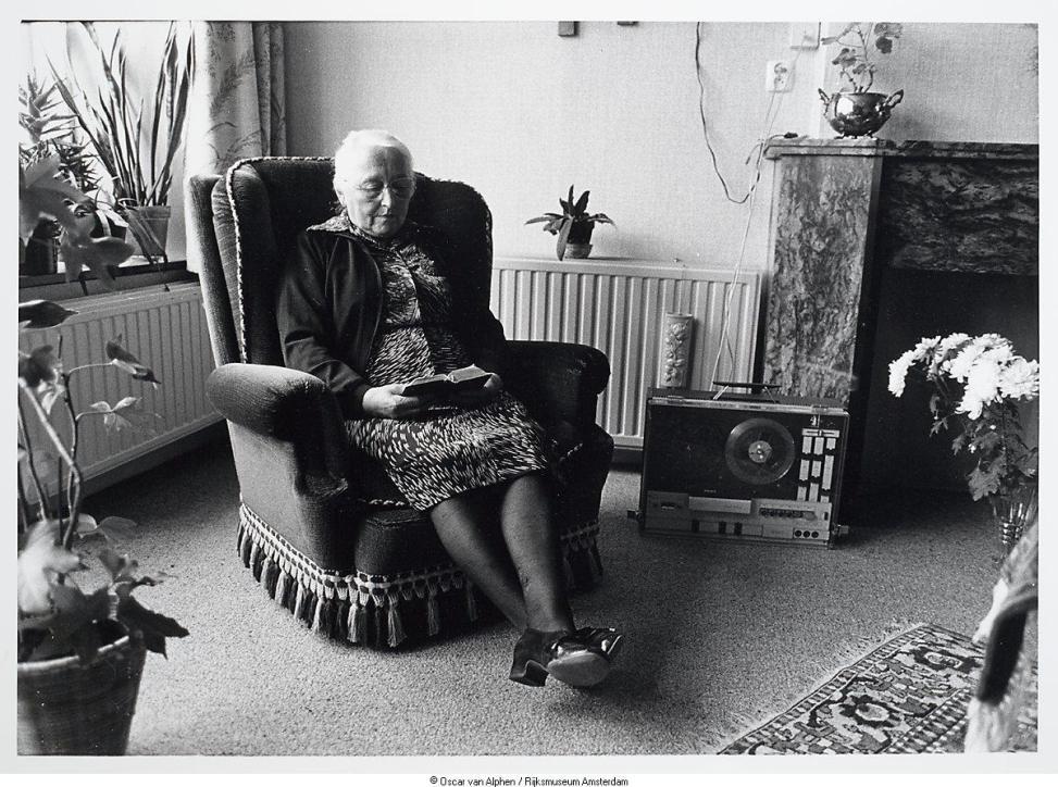 Oude dame luistert thuis via de Kerktelefoon naar de avondoverdenking