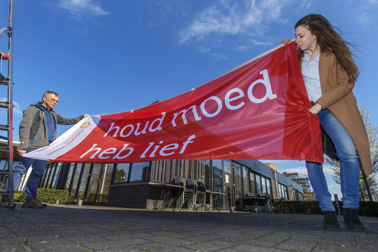 Ds. Anne-Meta Kobes en Tonny van Balen, beheerder van kerkgebouw Trinitas, hingen gisteren samen de vlag op | Foto: Rens Hooyenga, Friesh Dagblad
